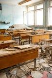 La scuola gettata e distrutta in Pripyat dopo l'incidente di Cernobyl in Ucraina nel 1986 Scrittori della scuola e manuali sparsi fotografia stock libera da diritti