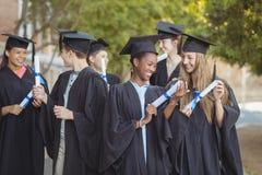 La scuola post-laurea scherza la condizione con il rotolo di grado in città universitaria alla scuola Fotografie Stock Libere da Diritti