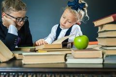 La scuola scherza la lettura del libro alla biblioteca Fotografia Stock Libera da Diritti