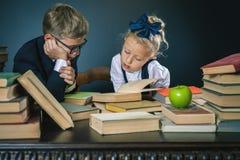 La scuola scherza la lettura del libro alla biblioteca Fotografie Stock Libere da Diritti