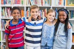 La scuola sorridente scherza la condizione con il braccio intorno in biblioteca immagine stock libera da diritti