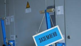 La señal de peligro cuelga en puerta del dispositivo de distribución en la estación eléctrica almacen de metraje de vídeo