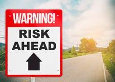 La señal de peligro en el camino a continuación dice riesgo a continuación Fotografía de archivo