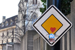 La señal de tráfico con las etiquetas engomadas Fotografía de archivo libre de regalías