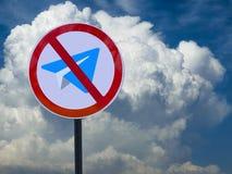 La señal de tráfico cruzó hacia fuera el avión contra el cielo con las nubes Pare el telegrama fotografía de archivo