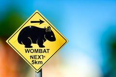 La señal de tráfico en el lado del camino advierte los conductores sobre wombat Fotografía de archivo libre de regalías