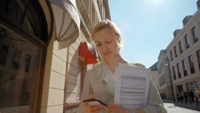 La señora acertada agradable del negocio está caminando en calle con los documentos y Smartphone almacen de metraje de vídeo