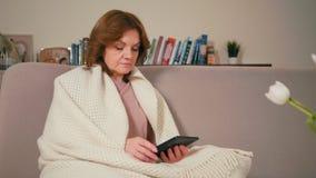 La señora adulta está leyendo el eBook usando la tableta en un cuarto acogedor con los libros tradicionales metrajes
