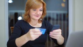 La señora adulta está pagando en línea usando Smartphone y la tarjeta de banco de crédito Byuing en casa almacen de video