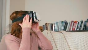 La señora adulta está utilizando los vidrios de VR que se sientan en el sofá en casa para jugar al videojuego almacen de metraje de vídeo