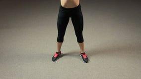 La señora apta con el cuerpo muscular fuerte que hace las posiciones en cuclillas con el barbell, finales ejercita metrajes