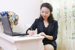 La señora asiática de la oficina toma notas foto de archivo libre de regalías