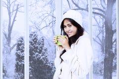 La señora asiática en abrigo de invierno disfruta de la bebida caliente Imagenes de archivo