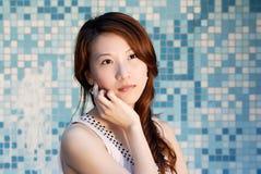 La señora asiática hermosa delante del mosaico y piensa Foto de archivo