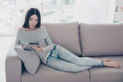 La señora asiática joven seria es el estudiar, siiting abajo en un bei acogedor Imágenes de archivo libres de regalías