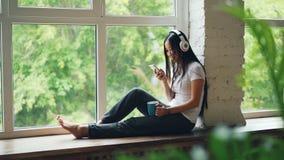 La señora asiática relajada se está sentando en el travesaño de la ventana, escuchando la música a través de los auriculares inal almacen de video