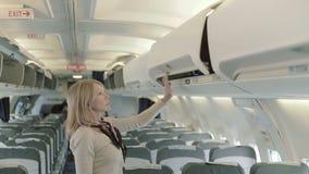 La señora bastante joven pone su equipaje al estante en el aeroplano almacen de video