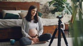 La señora bastante joven que cuenta con la madre y el vlogger popular está registrando el vídeo para el blog en línea que se sien almacen de metraje de vídeo
