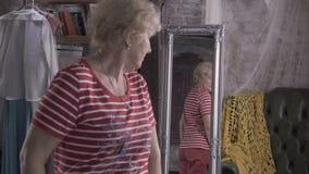 La señora bastante mayor arregla delante del espejo almacen de metraje de vídeo