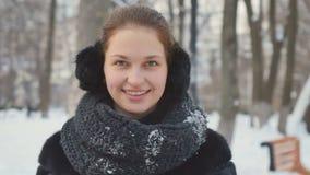 La señora bonita agita sus manos en manoplas a la cámara en el fondo del parque del invierno almacen de metraje de vídeo