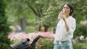 La señora bonita bebe el agua cerca del carro de bebé almacen de video