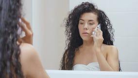 La señora bonita habla en el teléfono delante del espejo en el cuarto de baño almacen de video