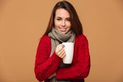 La señora caucásica feliz se vistió en suéter que bebía té caliente Fotos de archivo