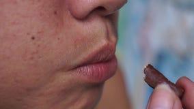 La señora come el pan del palillo del chocolate almacen de metraje de vídeo