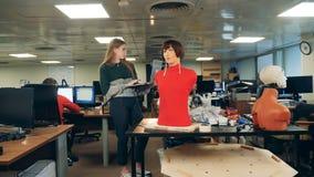 La señora con un ordenador portátil está observando a un maniquí femenino que habla almacen de metraje de vídeo