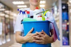 La señora de la limpieza con los productos de un cubo y de limpieza es imagen de archivo