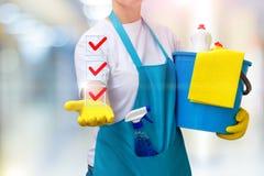 La señora de la limpieza muestra una lista de tareas terminadas Foto de archivo