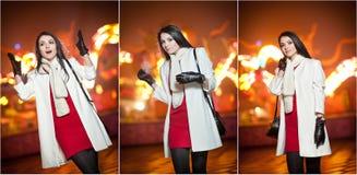 La señora de moda que lleva el vestido rojo y la capa blanca al aire libre en paisaje urbano con la ciudad se enciende en fondo R Imagen de archivo libre de regalías