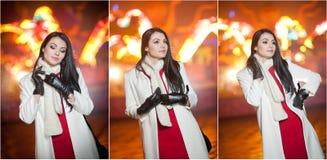 La señora de moda que lleva el vestido rojo y la capa blanca al aire libre en paisaje urbano con la ciudad se enciende en fondo R Imagen de archivo