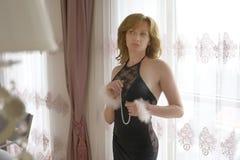 La señora de moda se vistió en la igualación del vestido negro del cordón Mujer joven que presenta en la actitud sensual que sost Imagen de archivo libre de regalías