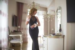 La señora de moda se vistió en la igualación del vestido negro del cordón Mujer joven que presenta en la actitud sensual que sost Imagenes de archivo