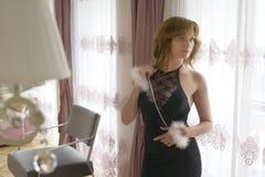 La señora de moda se vistió en la igualación del vestido negro del cordón Mujer joven que presenta en la actitud sensual que sost Fotos de archivo