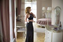 La señora de moda se vistió en la igualación del vestido negro del cordón Mujer joven que presenta en la actitud sensual que sost Foto de archivo libre de regalías