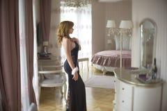 La señora de moda se vistió en la igualación del vestido negro del cordón Mujer joven que presenta en la actitud sensual que sost Imágenes de archivo libres de regalías