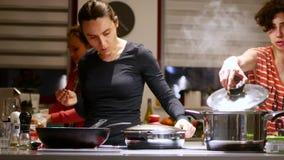 La señora de la mujer prepara la comida en la cocina en la compañía de sus amigos