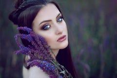 La señora de ojos azules hermosa con perfecto compone y peinado trenzado que se sienta en el campo y que sostiene las flores púrp foto de archivo