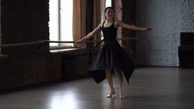 La señora de la tolerancia en vestido negro hace el torneado en estudio de la danza almacen de video