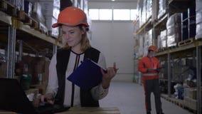 La señora del empleado en casco utiliza el ordenador portátil y hace notas en libreta en el fondo del trabajador del almacén metrajes