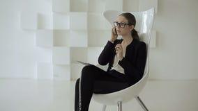 La señora del negocio se sienta en una silla blanca con una tableta de la PC y habla en su móvil en una oficina almacen de metraje de vídeo