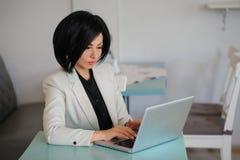 La señora del negocio se vistió en el traje blanco que trabajaba en un ordenador portátil Fotografía de archivo libre de regalías
