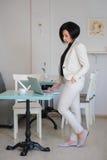 La señora del negocio se vistió en el traje blanco que trabajaba en un ordenador portátil Foto de archivo libre de regalías
