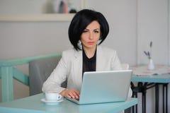 La señora del negocio se vistió en el traje blanco que trabajaba en un ordenador portátil Fotografía de archivo