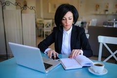 La señora del negocio se vistió en el traje negro que trabajaba en un ordenador portátil Imagen de archivo libre de regalías