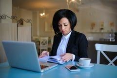 La señora del negocio se vistió en el traje negro que trabajaba en un ordenador portátil Imagen de archivo