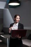 La señora del negocio se vistió en traje y con el ordenador portátil; Foto de archivo libre de regalías