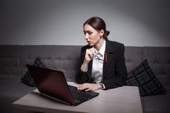 La señora del negocio se vistió en traje y con el ordenador portátil; Imagenes de archivo